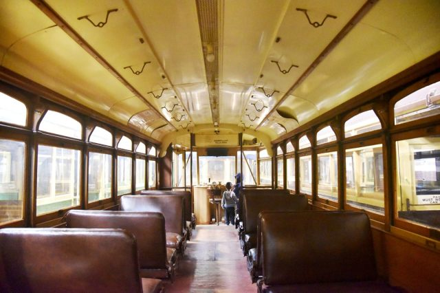 Children survey the controls of an historic arched roof tram.